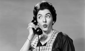 1950s Woman wearing apron talking on telephone with exaggerated surprised expression.