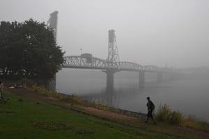 A man walks along the banks of the Williamette River in downtown Portland, Oregon where air quality due to smoke from wildfires was measured to be amongst the worst in the world.