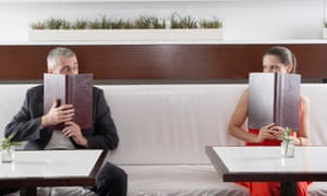 man and woman peering over menus