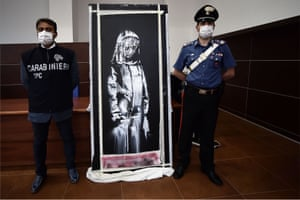 Carabinieri in L'Aquila, Italy, pose next to an artwork attributed to Banksy, which was stolen from outside the Bataclan concert hall in Paris