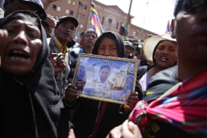 A woman holds up a photograph of one of the deceased.