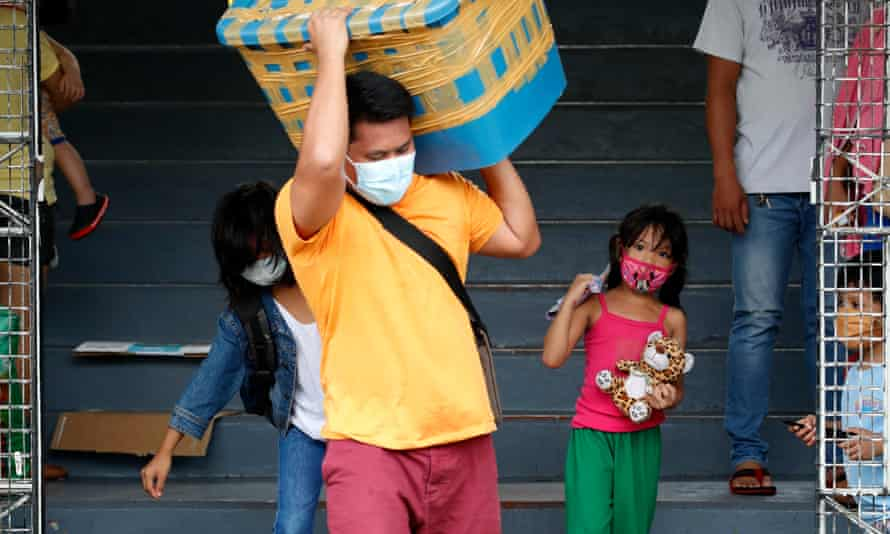 Stranded Filipino workers take their belongings to a gym in Manila.