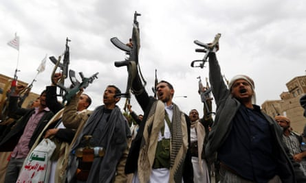 Armed Houthi members hold their guns in the air in Sana'a.