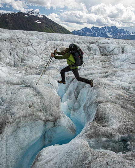 A climber jumps over a glacial stream on the Ruth Glacier in Denali national park.