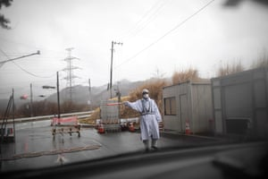 A guard gesturing at a checkpost exit from the exclusion zone of Futaba town, Fukushima prefecture.