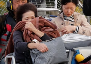 A woman reacts after she was rescued from a flooded area in the aftermath of Typhoon Hagibis, which caused severe floods at the Chikuma River in Nagano Prefecture, Japan, October 14, 2019.