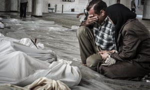 A mother and father weep over their child's body who was killed in a chemical weapons attack on the Damascus suburb of Ghouta.