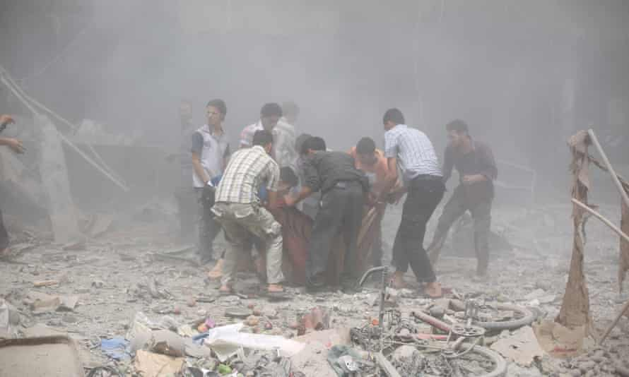 People carry the wounded to hospital after the air strike on Douma's souk in August.