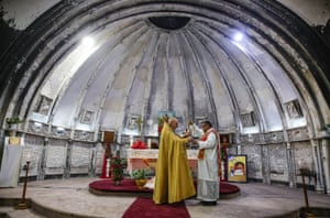 An Iraqi Syriac Catholic priest leads Christmas morning mass at the Mar Behnam and Mart Sarah Syriac Catholic Church, which was damaged and defaced during its occupation by Isis fighters