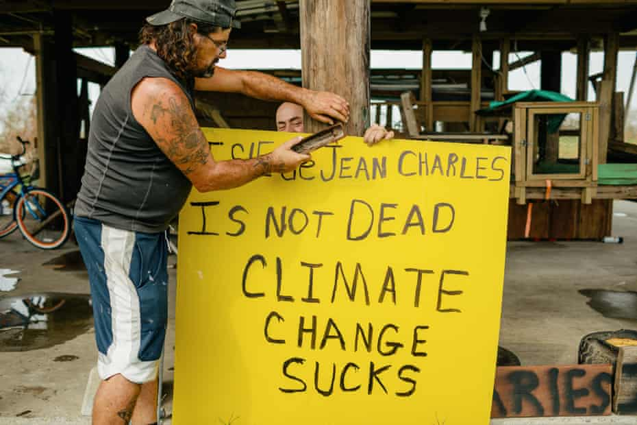 Ronald Chiasson helps his friend Chris Brunet nail a sign up that Brunet made to hang in the front of his home. the sign says Isle de Jean Charle is not dead - climate change sucks