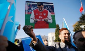 A demonstrator in Istanbul holds up a picture of Arsenal's Mesut Özil who expressed his horror at China's treatment of the Uighurs.