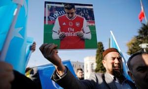 A Uighur demonstrator holds up an image of Arsenal's Mesut Özil in Istanbul on 14 December.