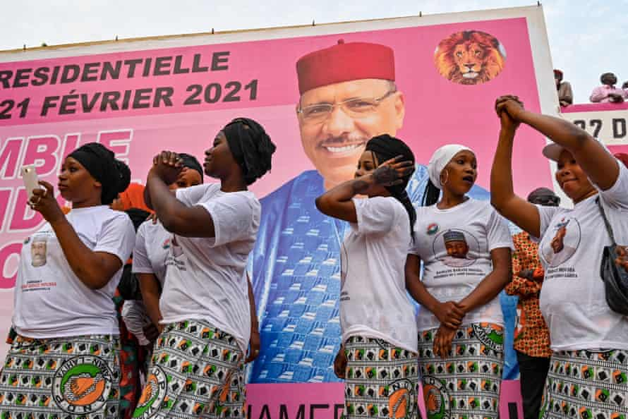 Supporters dance next to a poster during the coalition campaign rally of Mohamed Bazoum, who won a landslide victory on 23 February.
