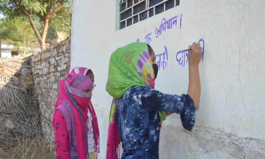 Writing slogans demanding free education for all girls until at least grade 12 on the walls in a Karauli village.