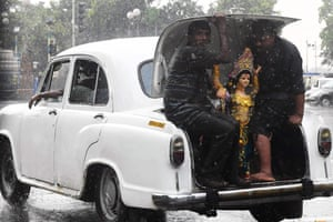 Kolkata, IndiaHindu devotees sit in the boot of a Hindustan Ambassador car with a statue of the Hindu deity Vishwakarma as they transport it in the rain for an immersion ceremony