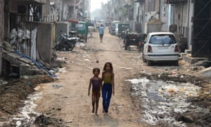 Indian girls walk along a street near a garbage site in the Indian capital, Delhi.