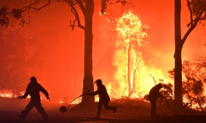 RFS volunteers and NSW Fire and Rescue officers fight a bushfire encroaching on properties near Termeil on the Princes Highway between Bateman's Bay and Ulladulla south of Sydney,Tuesday, December, 3, 2019. (AAP Image/Dean Lewins) NO ARCHIVING