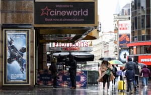 People walk past a Cineworld in Leicester's Square in London.
