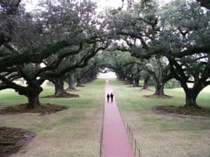 View from the balcony of the Oak Alley Plantation house, Louisiana, looking down at a couple strolling through the trees