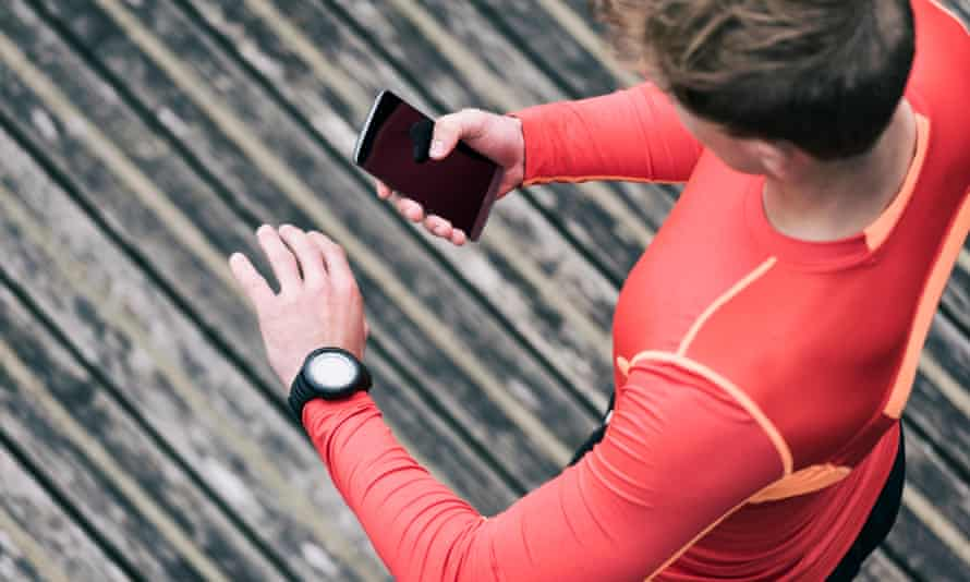 A runner checks his sport performance on his mobile phone and smartwatch