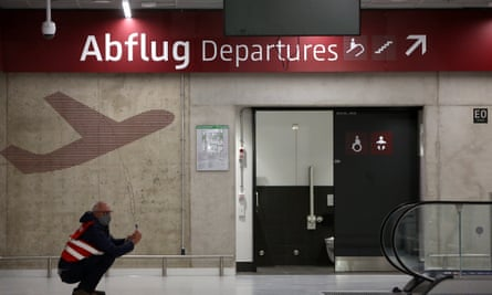 A visitor crouching taking a photo in Berlin-Brandenburg Willy Brandt Airport. The airport, originally scheduled to open in 2011, five years after building began in 2006, was delayed due to faulty construction planning, management issues, and corruption.