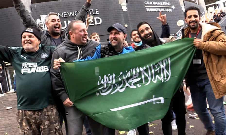 Jubilant Newcastle United fans hold a Saudi flag outside St James' Park.