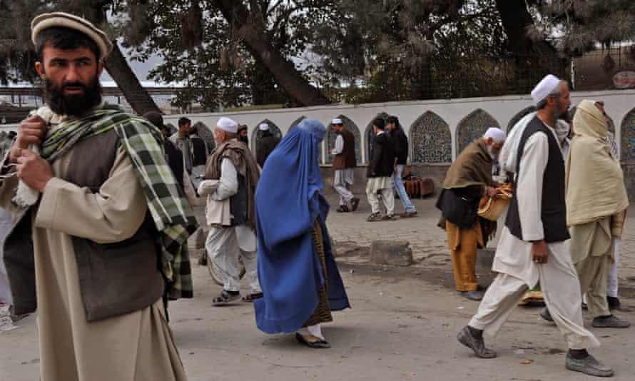 A burqa-clad Afghan woman walks among men in a market in Kabul