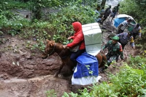Indonesian army and police guard ballot boxes and election materials during their distribution to Meru Betiri National Park on horseback in Jember, East Java province.