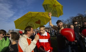 """Demonstrators hold umbrellas reading """"Freedom"""" and """"Love"""" as several hundreds of people protested against the coronavirus lockdown and curfew in Amsterdam, Netherlands, Sunday, Feb. 21, 2021."""