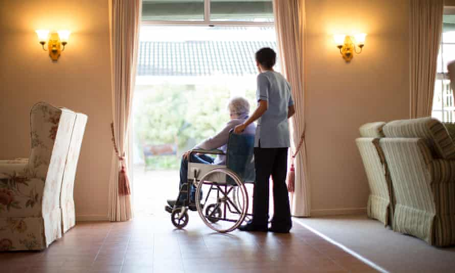 Care home Nnrse pushing patient in wheelchair