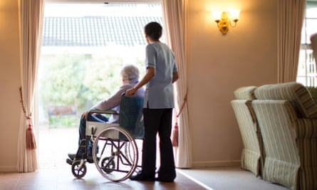 A nurse pushing patient in wheelchair in a care home.