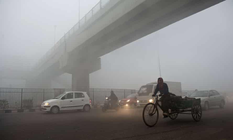 An Indian rickshaw puller passes under a bridge in Delhi, where air quality is ranked 'very poor'.