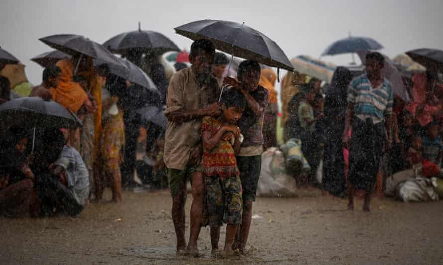 Rohingya refugees shelter from torrential rain after crossing the border into Bangladesh
