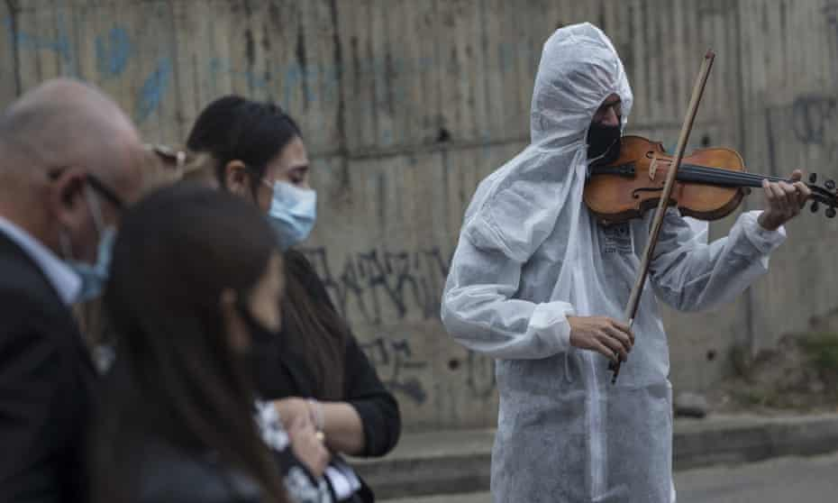Violinist Antonio Hernández performs for the relatives of a Covid-19 victim at Serafin cemetery in Bogota last week.