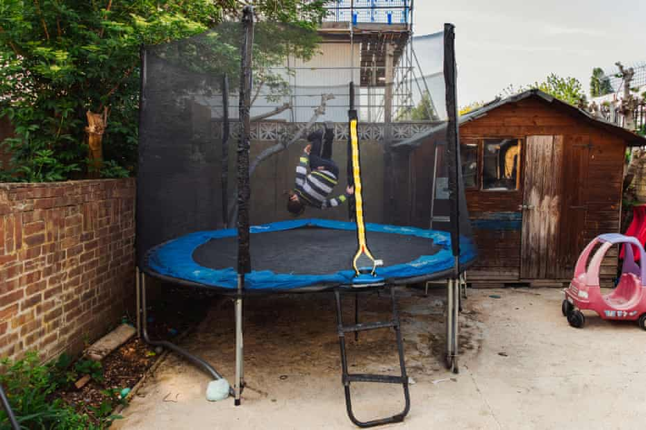 Betzalel turns a somersault on the trampoline in his garden
