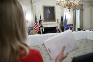CBS White House correspondent Paula Reid holds a copy of John Bolton's book as she asks a question of Donald Trump at the White House.