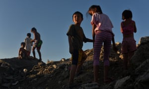 Children playing on a hill of garbage in the Philippines