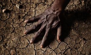 A man in South Sudan's Upper Nile state places his hand on parched soil