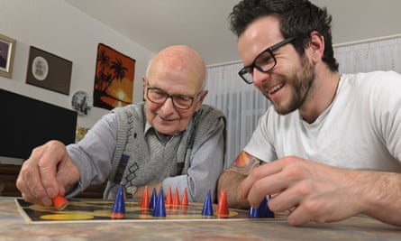 Two men, one elderly and one younger, playing board game together