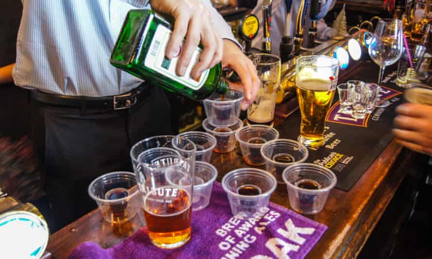 A barman pouring Jagerbombs at the bar at Travellers Friend, ('The Spivs'), pub, Woodford Green, Essex, England