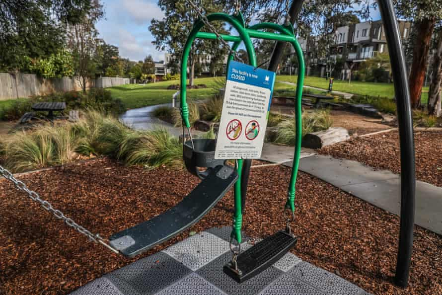 Two swings sit tied together with a sign advising the closure of a playground in the local government area of Monash in Melbourne on Tuesday.