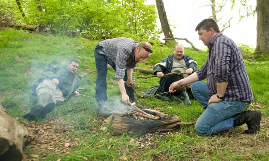 Volunteers roasting marshmallows around a fire at Cathkin Braes Country Patk.