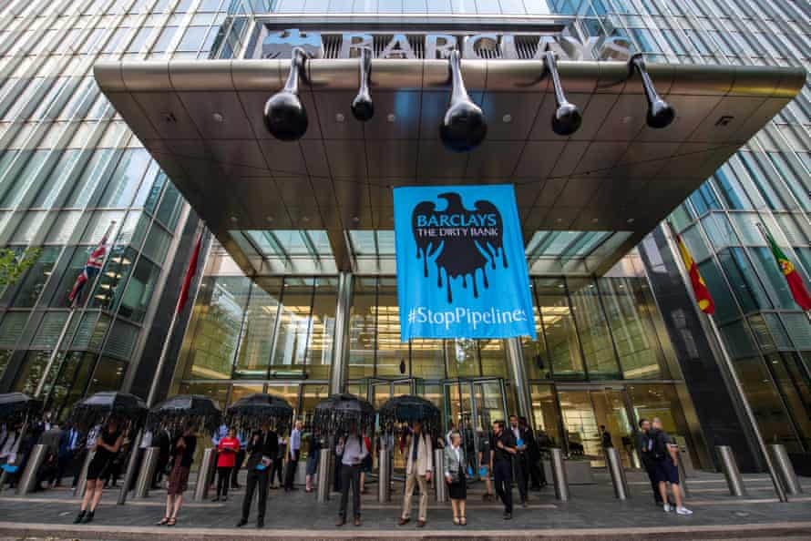 Greenpeace activists put up a banner showing the Barclays logo dripping with oil at its office in London.