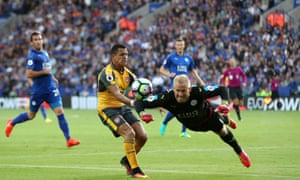 Leicester City goalkeeper Kasper Schmeichel beats Arsenal's Alexis Sanchez to the ball to clear it from danger.