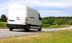 white van being driven on country road