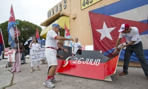 Protesters against the opening of the U.S. embassy in Havana demolish a 26th of July Movement placard, associated with the Castro revolution, during a demonstration in the Little Havana neighborhood on Friday.