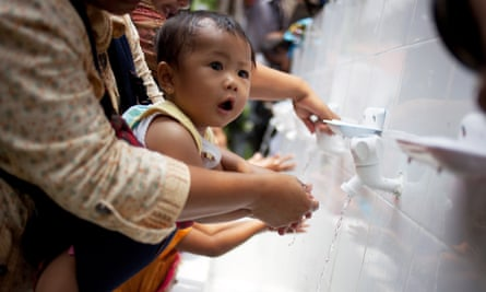 A mother helps her baby wash her hands.