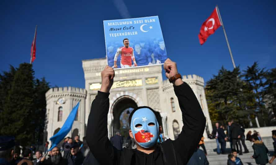 A supporter of Mesut Ozil's tweet about China's Uighur Muslims at a demonstration in Istanbul, holding a placard that reads 'Thanks for being our voice', 17 December 2019.