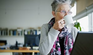 A businesswoman with grey hair sitting at a laptop drinking coffee