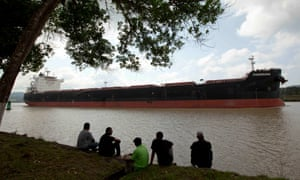 Men sit by the side of the Panama canal as a ship sails past.